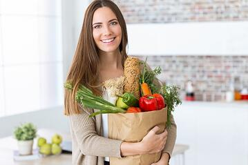 beautiful-young-woman-with-vegetables-in-grocery-bag-at-home_1301-7672.jpg
