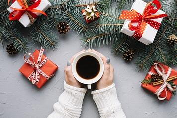 christmas-composition-with-hands-holding-coffee-and-presents_23-2147722785.jpg