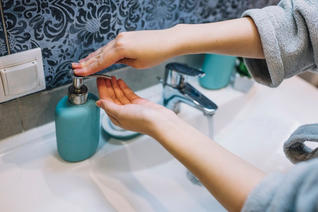 crop-woman-pouring-soap-on-hand_23-2147787912