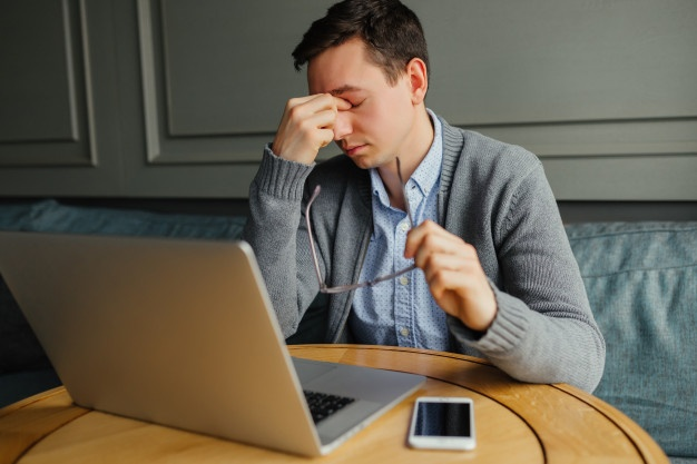 frustrated-young-man-massaging-his-nose-and-keeping-eyes-closed-while-working_8353-5961