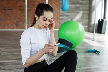 girl-works-with-her-smartphone-after-or-before-a-work-out-in-the-gym_8353-5534