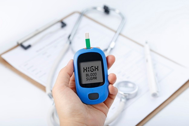 hand-holding-a-blood-glucose-meter-measuring-blood-sugar-the-background-is-a-stethoscope-and-chart-file_1387-936