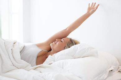 happy-young-woman-stretching-in-bed-after-sleep_1262-5199.jpg