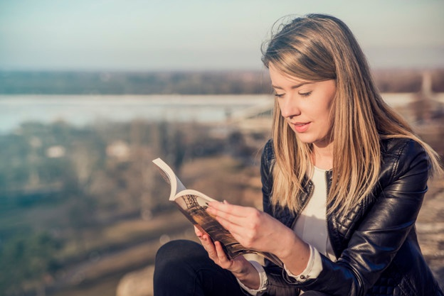 reading-her-favorite-book-beautiful-young-woman-reading-book-and-smiling-while-sitting-outdoors-landscape-on-the-background-reading-a-book-concept_1391-384.jpg