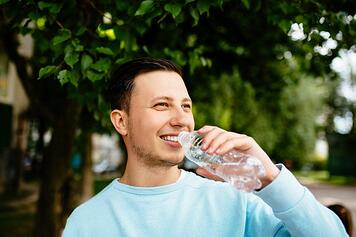 smiling-man-drinks-water-from-bottle-on-the-background-of-green-tree-in-summer-day_8353-7016