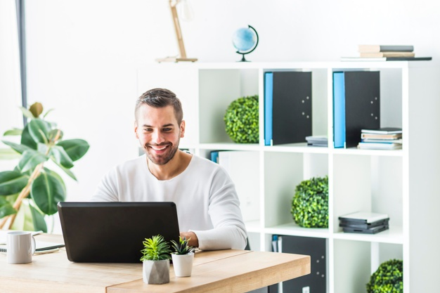 smiling-young-businessman-using-laptop-in-office_23-2147839980