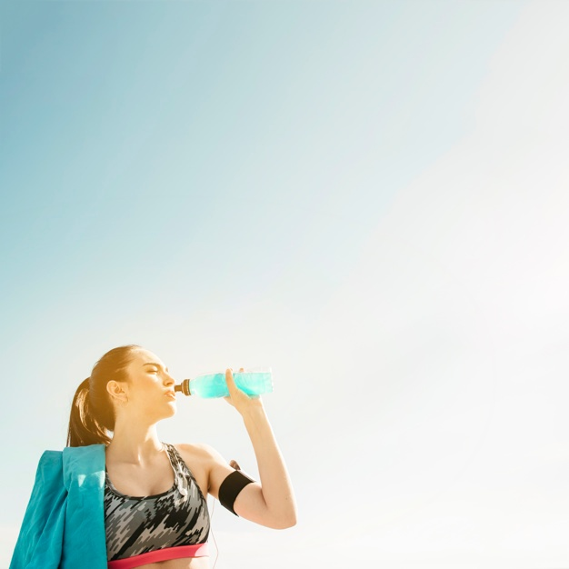 sporty-woman-drinking-from-bottle-on-sky-background_23-2147827083