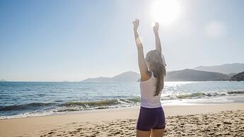 woman-stretching-arms-at-the-beach_23-2147665313