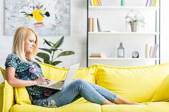 woman-using-laptop-sitting-on-sofa_23-2147862347