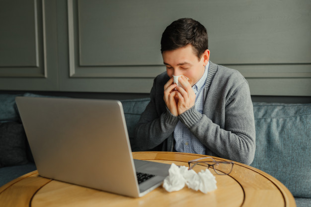 young-business-man-blows-his-nose-while-working-at-his-laptop-in-the-workplace_8353-5963